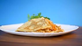 Λεπτύντε τις τηγανισμένες τηγανίτες που γεμίζονται με το μαγειρευμένο λάχανο σε ένα πιάτο φιλμ μικρού μήκους