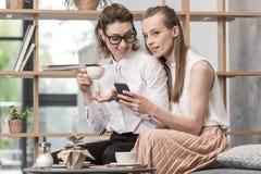 Λεσβιακός καφές κατανάλωσης ζευγών και χρησιμοποίηση του smartphone από κοινού Στοκ φωτογραφία με δικαίωμα ελεύθερης χρήσης