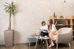 Λεσβιακός καφές κατανάλωσης ζευγών και χρησιμοποίηση του smartphone από κοινού Στοκ εικόνες με δικαίωμα ελεύθερης χρήσης