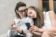 Λεσβιακός καφές κατανάλωσης ζευγών και χρησιμοποίηση του smartphone από κοινού Στοκ Φωτογραφία