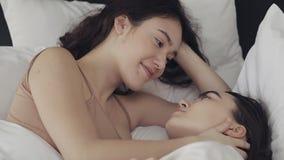 Λεσβιακό ζεύγος που αγκαλιάζει και που χαμογελά μαζί στο κρεβάτι στο σ φιλμ μικρού μήκους