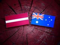 Λετονική σημαία με την αυστραλιανή σημαία σε ένα κολόβωμα δέντρων που απομονώνεται Στοκ εικόνες με δικαίωμα ελεύθερης χρήσης