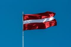 Λετονική σημαία που φυσά στο αεράκι Στοκ εικόνα με δικαίωμα ελεύθερης χρήσης