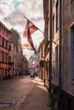 Λετονική σημαία στην οδό που φωτίζεται στον ήλιο Στοκ φωτογραφίες με δικαίωμα ελεύθερης χρήσης