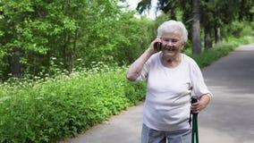 Λευκιά μαλλιαρή γιαγιά που μιλά στο τηλέφωνο με την οικογένεια απόθεμα βίντεο