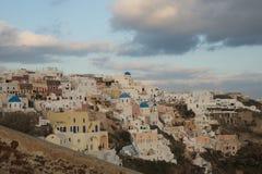 Λευκιά πόλη σε μια κλίση ενός λόφου στο ηλιοβασίλεμα, Oia, Santorini, Greec Στοκ Φωτογραφία
