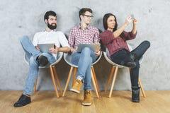 Λευκοί ενήλικοι που χρησιμοποιούν τις ηλεκτρονικές συσκευές Στοκ Φωτογραφία