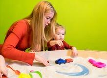 Λευκοί ευρωπαϊκοί άνθρωποι μητέρων και κορών που αναπτύσσουν τις μελέτες της πρόωρης ανάπτυξης με την άμμο στο Sandbox και περισσ Στοκ φωτογραφία με δικαίωμα ελεύθερης χρήσης