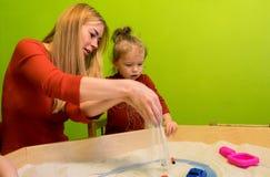 Λευκοί ευρωπαϊκοί άνθρωποι μητέρων και κορών που αναπτύσσουν τις μελέτες της πρόωρης ανάπτυξης με την άμμο στο Sandbox και περισσ Στοκ Εικόνες