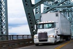 Λευκοί μεγάλοι ημι φορτηγό και σημαιοφόρος εγκαταστάσεων γεώτρησης στην αγροτική γέφυρα Στοκ Εικόνες
