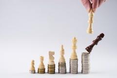 Λευκός βασιλιάς σκακιού που στέκεται στα συσσωρευμένα νομίσματα πέρα από το μαύρο βασιλιά Στοκ Εικόνες
