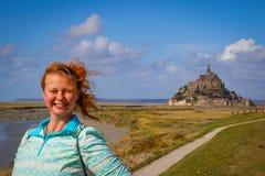 Λευκός νέος τουρίστας γυναικών με την κόκκινη τρίχα που χαμογελά ευτυχώς στα πλαίσια της κύριας έλξης της Γαλλίας του μεσαιωνικού στοκ εικόνες με δικαίωμα ελεύθερης χρήσης