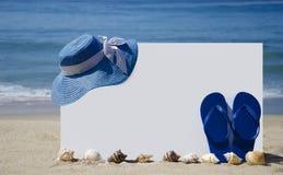 Λευκός πίνακας με τις σαγιονάρες και καπέλο στην αμμώδη παραλία Στοκ Εικόνες