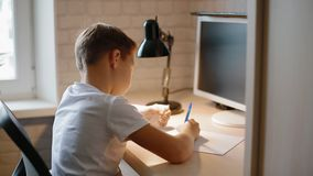 Λευκό αγόρι που κάνει το hometask του απόθεμα βίντεο