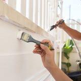 Λευκό ζωγραφικής βουρτσών εκμετάλλευσης εργαζομένων χεριών στοκ φωτογραφία
