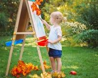 Λευκό καυκάσιο κορίτσι παιδιών παιδιών μικρών παιδιών που στέκεται έξω στο πάρκο θερινού φθινοπώρου που επισύρει την προσοχή ease Στοκ Εικόνες