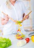 Λευκό κορίτσι που προετοιμάζει τη σαλάτα από τα φρέσκα λαχανικά στοκ εικόνες