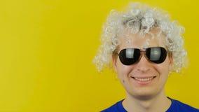 Λευκό σγουρό χαμογελώντας άτομο τρίχας με την αστεία και χαρωπά ανθρώπινη συγκίνηση μαύρων γυαλιών ηλίου, στο κίτρινο υπόβαθρο το απόθεμα βίντεο