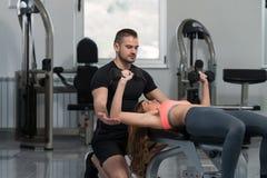 Λεωφορείο γυμναστικής που βοηθά τη γυναίκα στη θωρακική άσκηση Στοκ Εικόνες