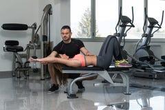 Λεωφορείο γυμναστικής που βοηθά τη γυναίκα στη θωρακική άσκηση Στοκ Εικόνα