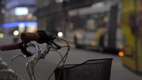 Λεωφορείο με τα φω'τα στους γύρους μέσω της πόλης Ποδηλάτες και πεζοί στην πόλη νύχτας απόθεμα βίντεο