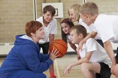 Λεωφορείο που δίνει τη συζήτηση ομάδας στο ομάδα μπάσκετ δημοτικού σχολείου στοκ εικόνα