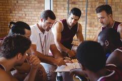 Λεωφορείο που εξηγεί το σχέδιο παιχνιδιού στα παίχτης μπάσκετ Στοκ Φωτογραφία