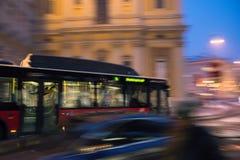 Λεωφορείο που κινείται γρήγορα στη θαμπάδα κινήσεων πόλεων νύχτας Στοκ Εικόνα