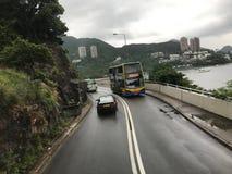 Λεωφορείο Χονγκ Κονγκ που αναρριχείται στο λόφο έξω από Repulse τον κόλπο στοκ εικόνα