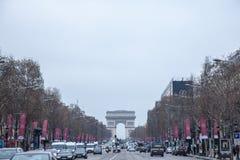 Λεωφόρος Elysees Champs με το τόξο de Triomphe στο υπόβαθρο κατά τη διάρκεια μιας νεφελώδους ομιχλώδους μολυσμένης ημέρας, με μια Στοκ φωτογραφία με δικαίωμα ελεύθερης χρήσης