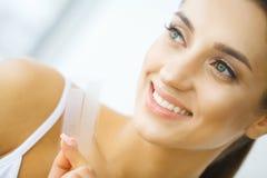 λεύκανση δοντιών Όμορφη χαμογελώντας εκμετάλλευση γυναικών που λευκαίνει τη λουρίδα στοκ φωτογραφία