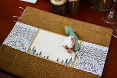 Λεύκωμα φωτογραφιών γαμήλιων ντεκόρ με τα δαχτυλίδια και το βαμβάκι κλαδίσκων Στοκ Εικόνα