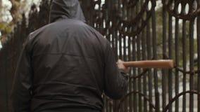 Ληστής στο ρόπαλο εκμετάλλευσης μασκών και περίπατος κατά μήκος του φράκτη σχαρών απόθεμα βίντεο