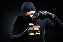 Ληστής balaclava που συσσωρεύει τις χρυσές ράβδους στοκ φωτογραφία με δικαίωμα ελεύθερης χρήσης