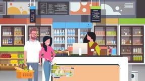 Λιανικός ταμίας γυναικών στους πελάτες ζευγών υπεραγορών ελέγχων που κρατούν το καλάθι με την αγορά παντοπωλείων έννοιας αγορών τ απεικόνιση αποθεμάτων