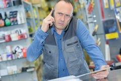 Λιανοπωλητής μπερδεμένη στην τηλέφωνο έκφραση στοκ φωτογραφία
