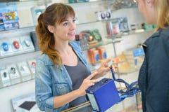 Λιανοπωλητής που παρουσιάζει ηλεκτρικό στοιχείο στον πελάτη στοκ εικόνα