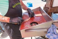 Λιανοπωλητής ψαριών που καθαρίζει τις νέες ρέγγες εποχής για την κατανάλωση στο στάβλο καταστημάτων του στοκ φωτογραφίες
