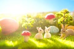 Λιβάδι άνοιξη με τα μικροσκοπικά κουνέλια Πάσχας και τα αυγά Πάσχας Στοκ εικόνες με δικαίωμα ελεύθερης χρήσης