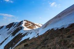 Λιβάδι με τα hummocks και τη χλόη Τοπίο με το λόφο, παγωμένα snowdrifts μπλε ουρανός σύννεφων Τοπίο άνοιξη Στοκ φωτογραφία με δικαίωμα ελεύθερης χρήσης