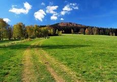 Λιβάδι με το ίχνος, τα δέντρα γύρω, το λόφο και το μπλε ουρανό πεζοπορίας με τα βουνά Beskydy σύννεφων την άνοιξη Στοκ Εικόνα