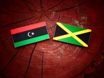Λιβυκή σημαία με την τζαμαϊκανή σημαία σε ένα κολόβωμα δέντρων Στοκ Εικόνες