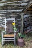 Λικνίζοντας καρέκλα στο αγρόκτημα που κοσμείται με έναν ηλίανθο στοκ εικόνα