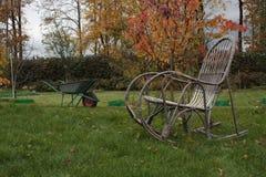 Λικνίζοντας καρέκλα και wheelbarrow στη χλόη Στοκ φωτογραφία με δικαίωμα ελεύθερης χρήσης