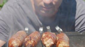 Λιπαρός ορεκτικός μάγειρας λουκάνικων στην πυρκαγιά Παχιές σταλαγματιές στην πυρκαγιά Πολύς καπνός από τους άνθρακες απόθεμα βίντεο