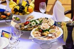 Λιχουδιές, πρόχειρα φαγητά και φρούτα στον εορταστικό πίνακα στο εστιατόριο Εορτασμός catering μήλων ανασκόπησης συμποσίου καλαθι στοκ φωτογραφία