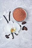 Λοβοί βανίλιας με ένα λουλούδι, μια σκόνη κακάου και τα φασόλια ως συστατικό για το ψήσιμο στοκ φωτογραφία