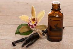Λοβοί βανίλιας, aromatherapy έλαιο και λουλούδια ορχιδεών στην ξύλινη πλάτη Στοκ Φωτογραφίες