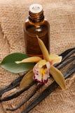 Λοβοί βανίλιας, aromatherapy έλαιο και λουλούδια ορχιδεών στο κλωστοϋφαντουργικό προϊόν Στοκ φωτογραφία με δικαίωμα ελεύθερης χρήσης