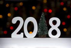 Λογαριάζει τη στάση του 2018 σε έναν άσπρο πίνακα σε ένα κλίμα κίτρινου και των κόκκινων φώτων bokeh αντί ενός ενιαίου χριστουγεν Στοκ εικόνα με δικαίωμα ελεύθερης χρήσης